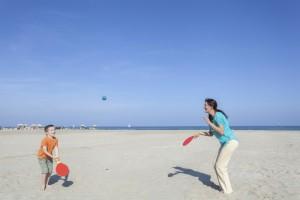 Familie spielt am Strand Tennis