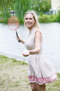 Schöne Frau spielt Tennis an einem See